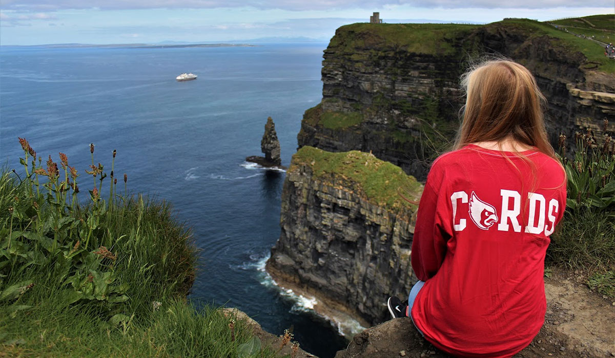 Student sitting on the edge of the Cliffs of Moher